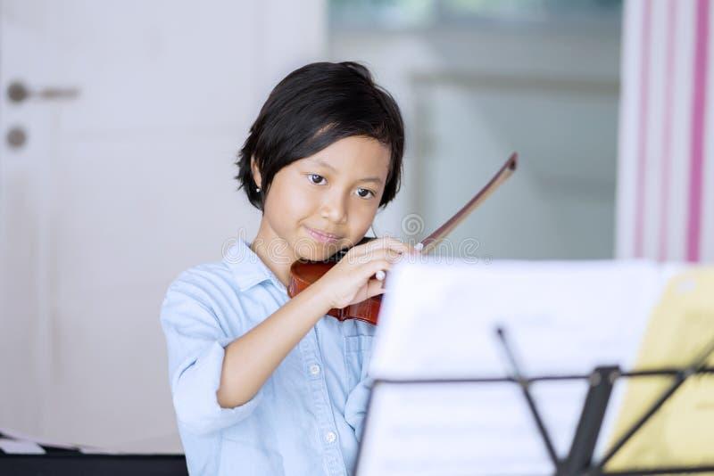 Niña que practica para tocar el violín en casa fotos de archivo libres de regalías
