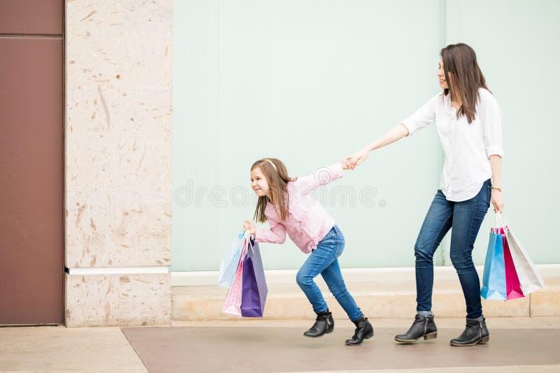 Niña que quita a su madre shopaholic hacia fuera de una tienda imágenes de archivo libres de regalías