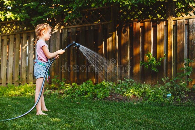 Niña que riega las plantas verdes en patio trasero imagen de archivo libre de regalías