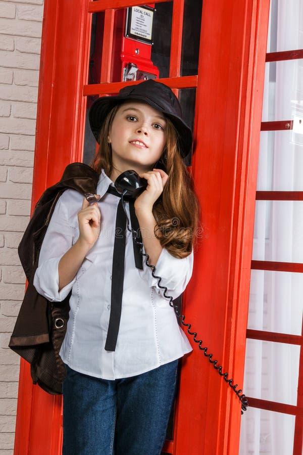 Niña que se coloca al lado de una cabina de teléfono imagen de archivo libre de regalías