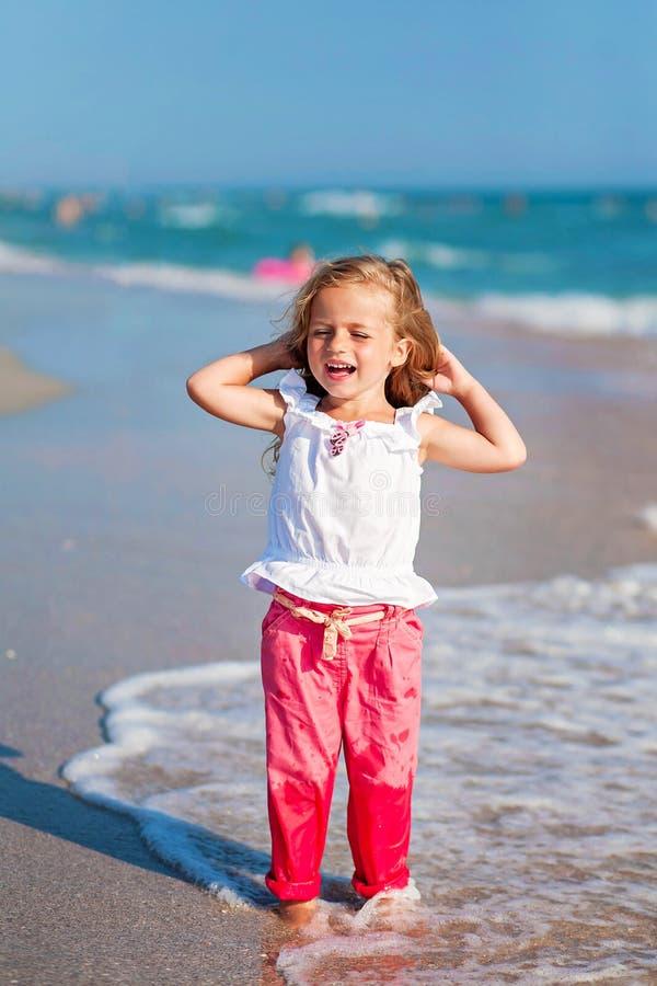 Niña que se coloca en la playa en pantalones rosados y laughting fotos de archivo libres de regalías