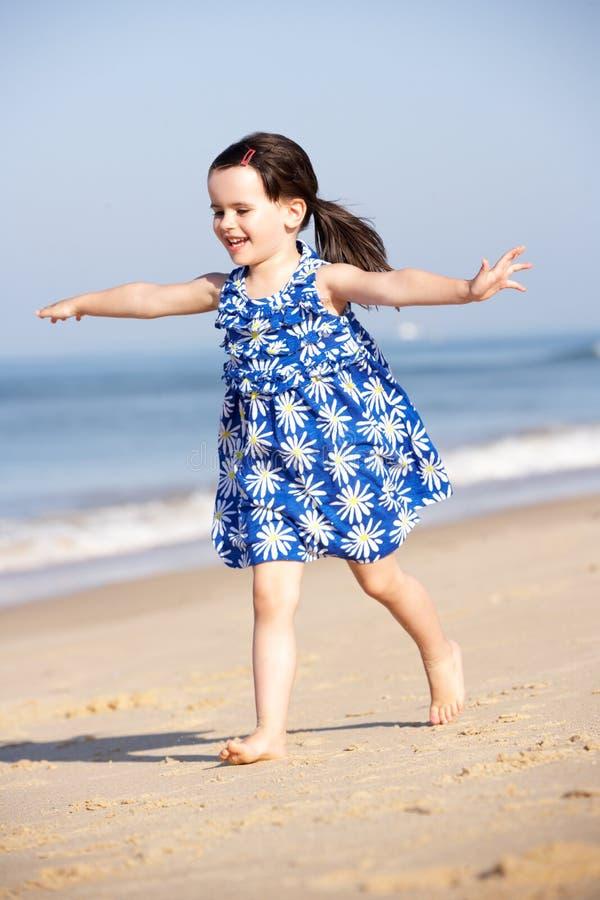 Niña que se ejecuta a lo largo de la playa imagen de archivo libre de regalías