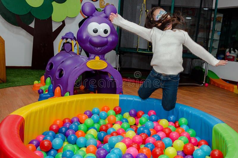 Niña que se lanza en una piscina por completo de bolas coloreadas foto de archivo