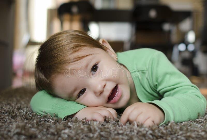 Niña que se relaja en la alfombra en su hogar imagen de archivo