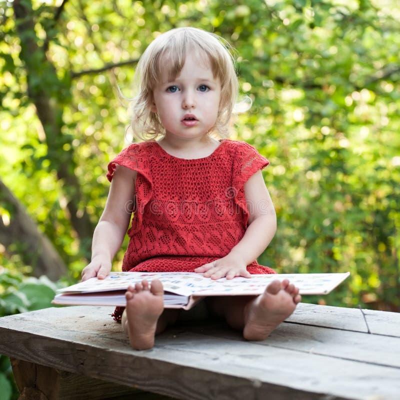 Niña que se sienta cuidadosamente en un banco con la opinión grande del primer del libro fotografía de archivo libre de regalías