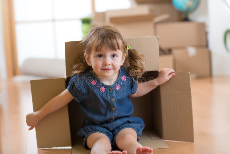 Niña que se sienta dentro de la caja de cartón en su nuevo hogar imagen de archivo libre de regalías
