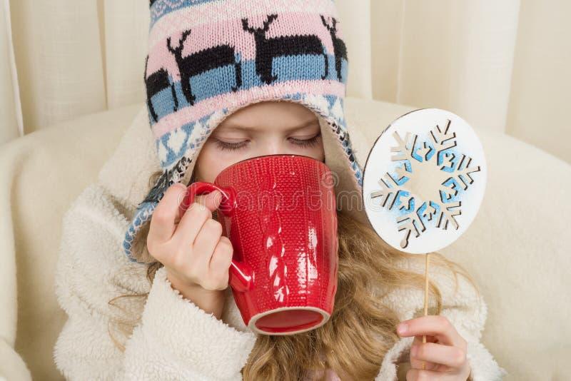 Niña que se sienta en casa en la silla, en sombrero hecho punto con el ornamento de la Navidad con la taza de bebida caliente Ten imágenes de archivo libres de regalías