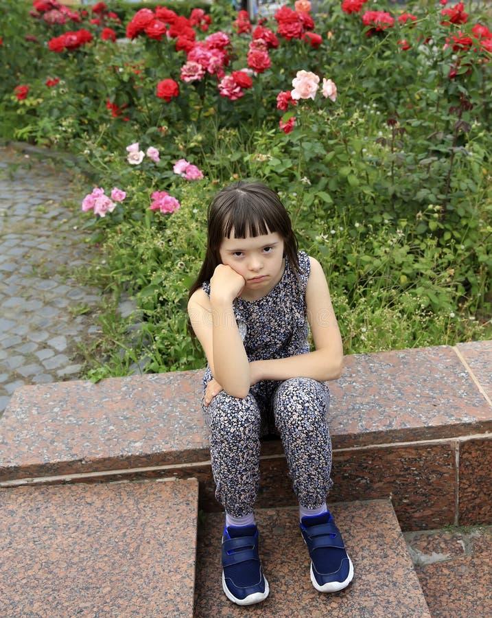 Niña que se sienta en el fondo del jardín imagen de archivo