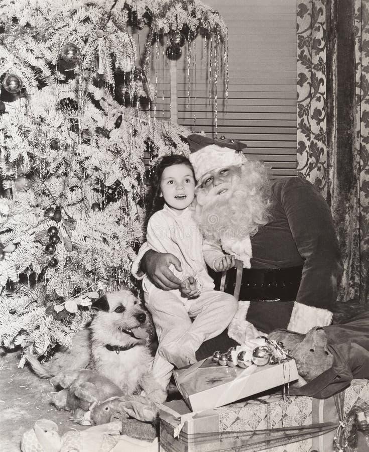 Niña que se sienta en el revestimiento de Papá Noel debajo del árbol de navidad fotos de archivo