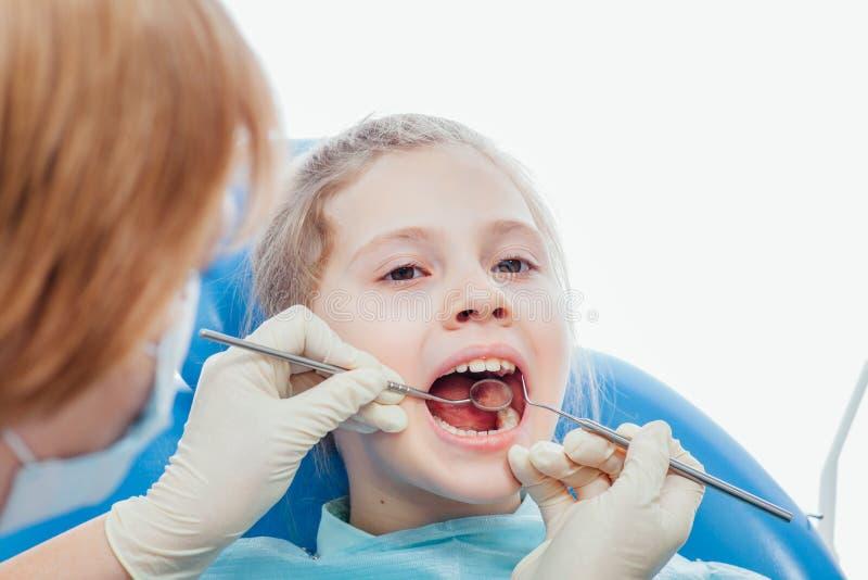 Niña que se sienta en la oficina de los dentistas fotos de archivo