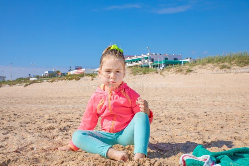 Niña que se sienta en la playa que mira con el exp desafiador fotos de archivo libres de regalías