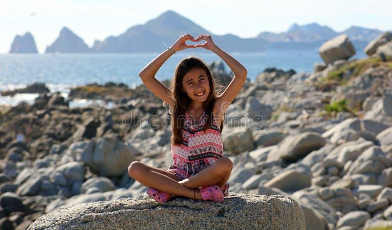 Niña que se sienta en las rocas en el frente de océano en el mar del acantilado del centro turístico de Los Cabos México imagenes de archivo