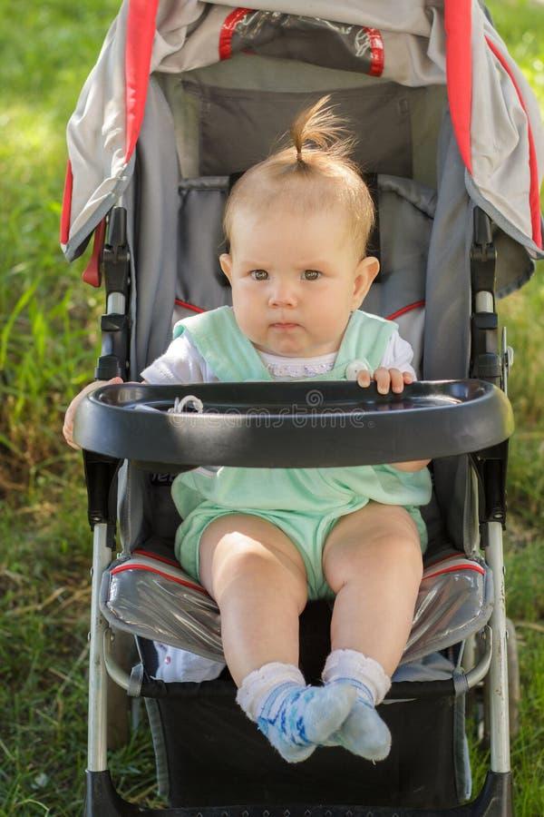 Niña que se sienta en un carro de bebé imagen de archivo libre de regalías