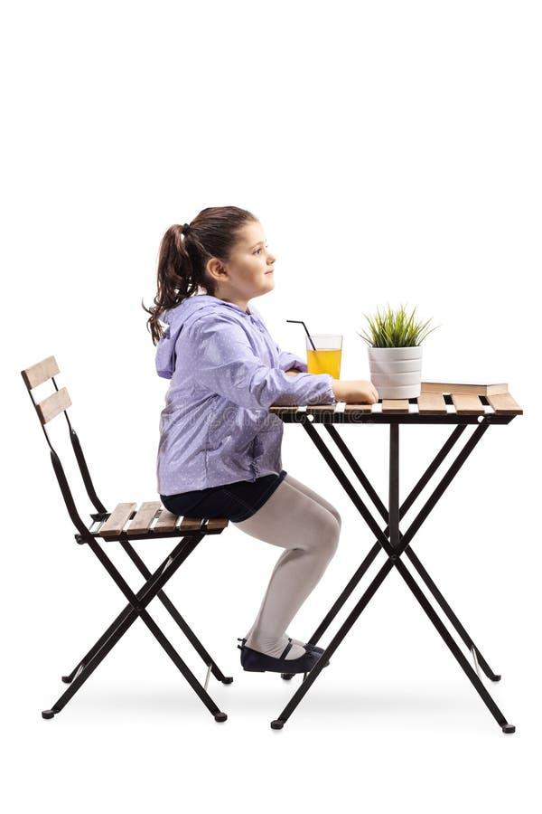 Niña que se sienta en una tabla de madera con un vidrio de zumo de naranja imágenes de archivo libres de regalías
