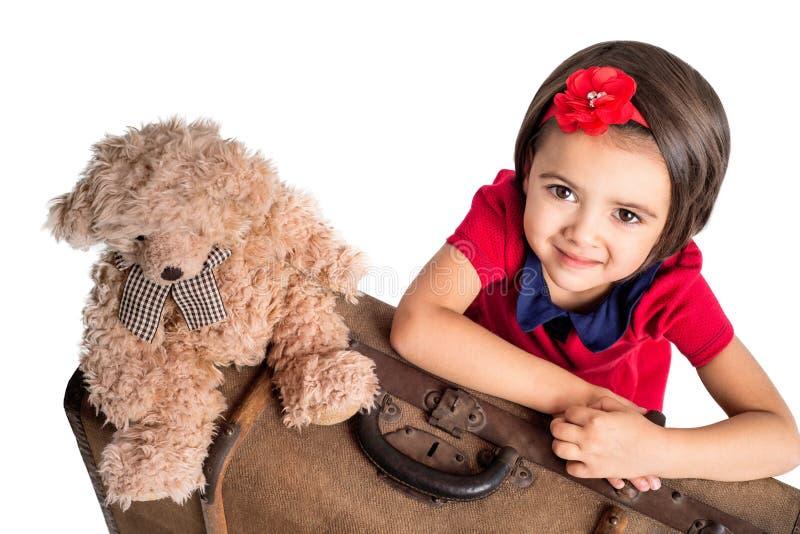 Niña que sonríe con el oso de la maleta y del juguete fotografía de archivo