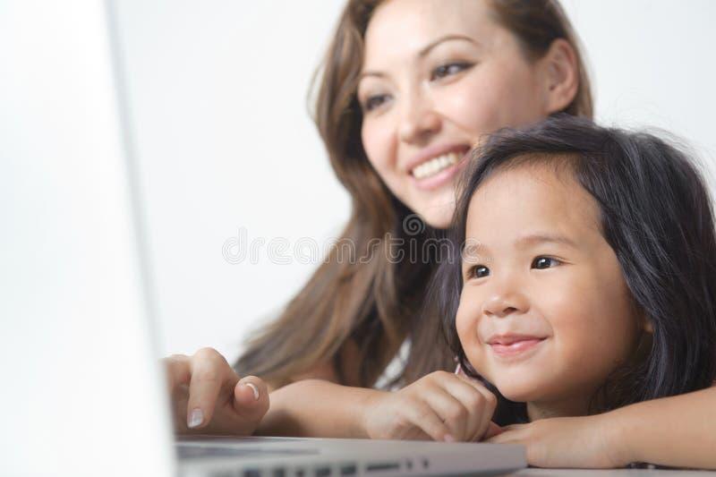 Niña que sonríe con la madre fotografía de archivo