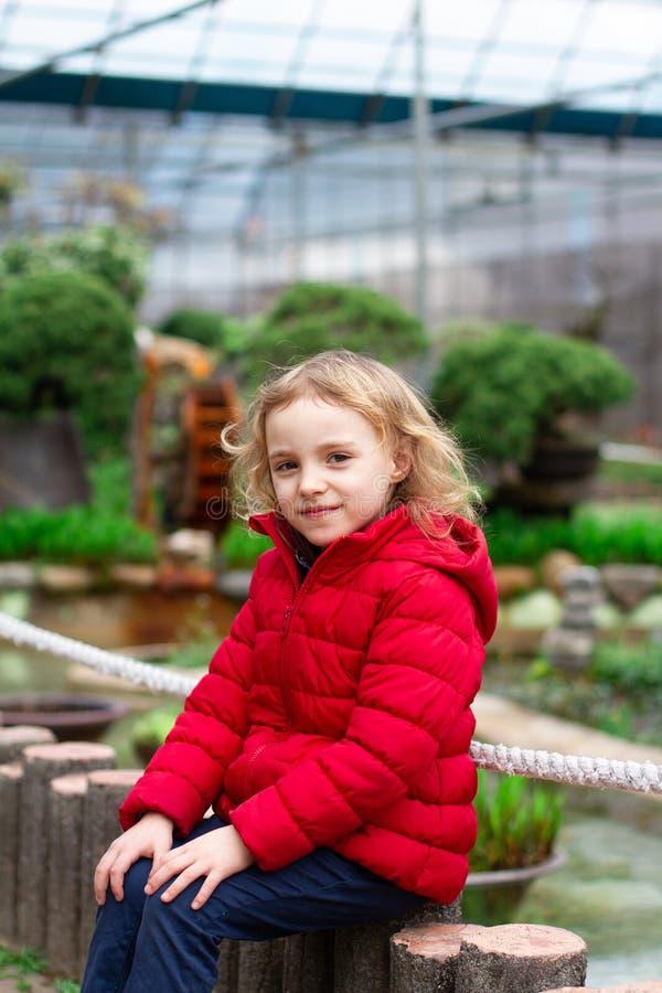 Niña que sonríe en una chaqueta roja en naturaleza fotos de archivo libres de regalías