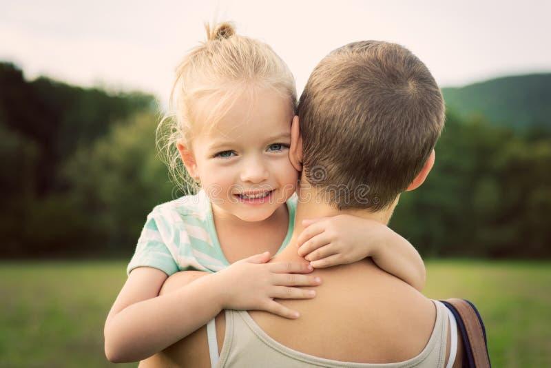 Niña que sonríe y que abraza a su madre fotografía de archivo