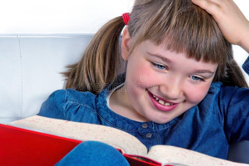 Niña que sonríe y que lee un libro foto de archivo libre de regalías