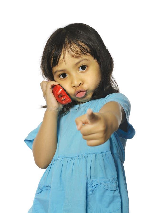 Niña que sostiene el teléfono inalámbrico rojo imagenes de archivo