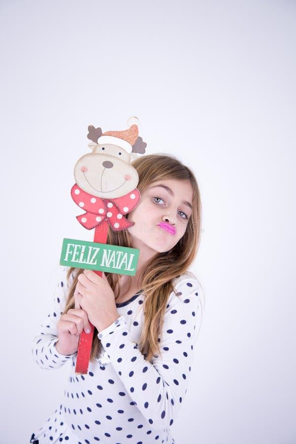 Niña que sostiene la placa de la Feliz Navidad foto de archivo