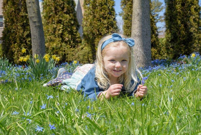 Niña que sostiene las flores en primavera imagenes de archivo