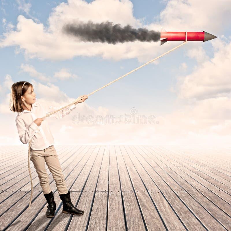 Niña que sostiene un cohete con una cuerda fotos de archivo