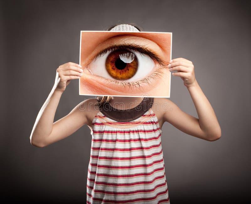 Niña que sostiene un ojo imagenes de archivo