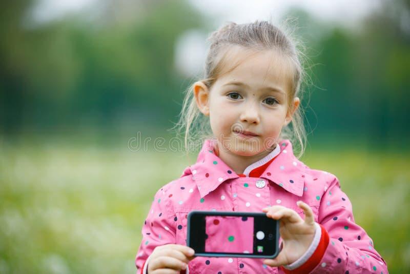 Niña que sostiene un teléfono elegante con la imagen en la exhibición foto de archivo libre de regalías