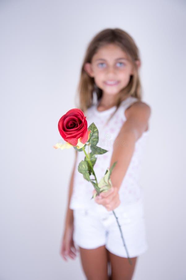 Niña que sostiene una flor roja que ofrece para usted fotografía de archivo