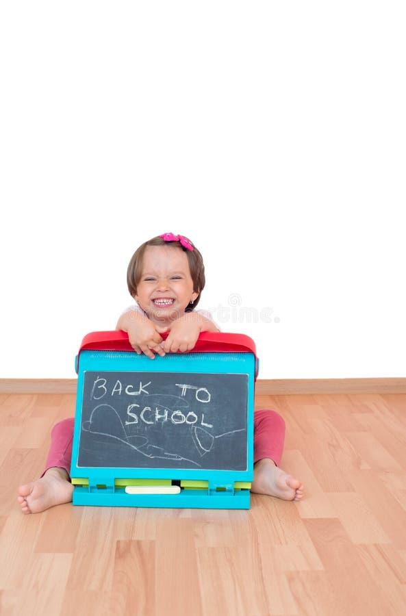 Niña que sostiene una pizarra con el texto de nuevo a la escuela escrita en ella, aislado imagenes de archivo