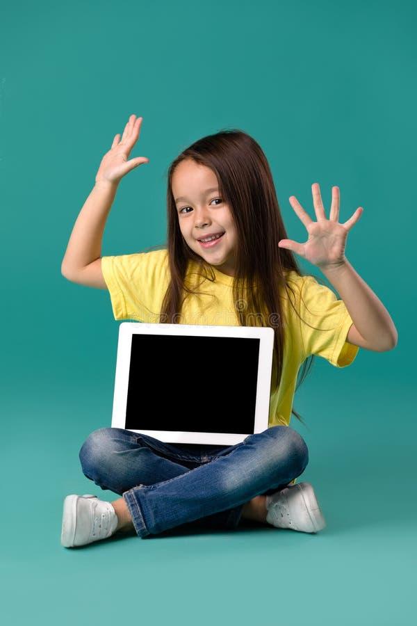 Niña que sostiene una tableta en blanco fotos de archivo libres de regalías