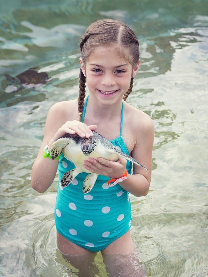 Niña que sostiene una tortuga de mar del bebé fotos de archivo