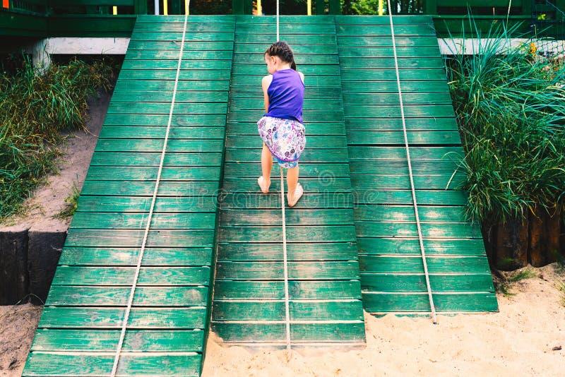 Niña que sube una pared de madera al aire libre en el playgroun de los niños imagenes de archivo