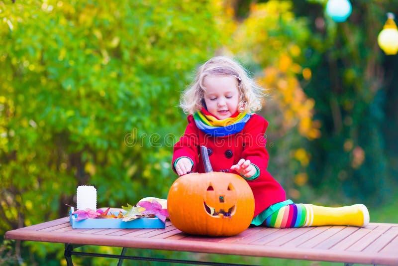 Niña que talla la calabaza en Halloween fotos de archivo