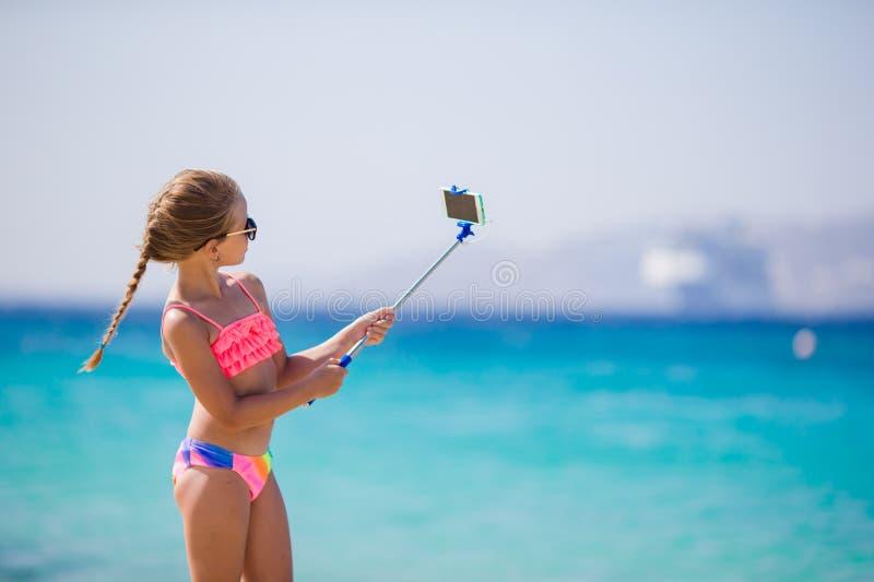 Niña que toma el retrato del selfie con su smartphone en la playa imágenes de archivo libres de regalías