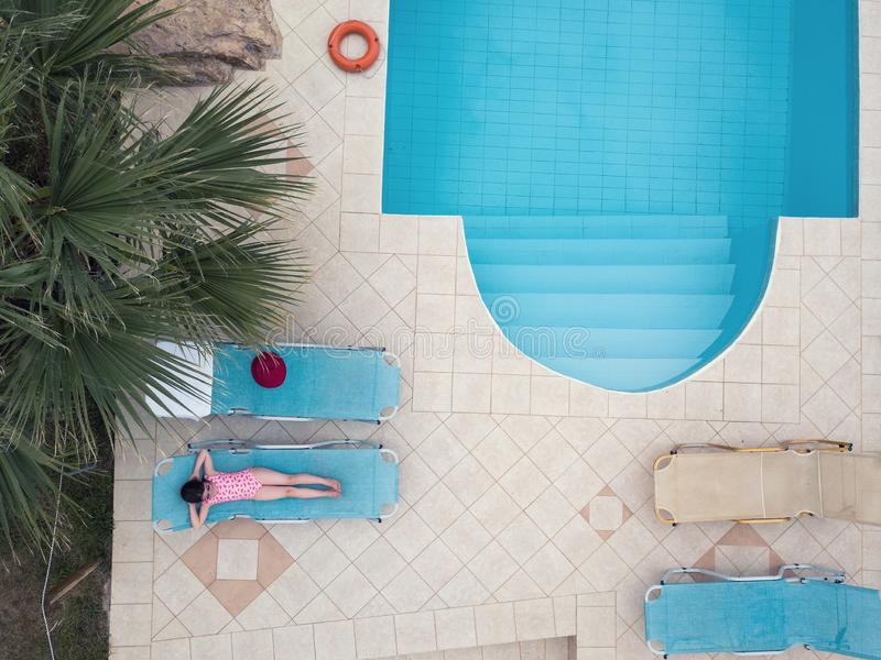 Niña que toma el sol por una piscina imagen de archivo