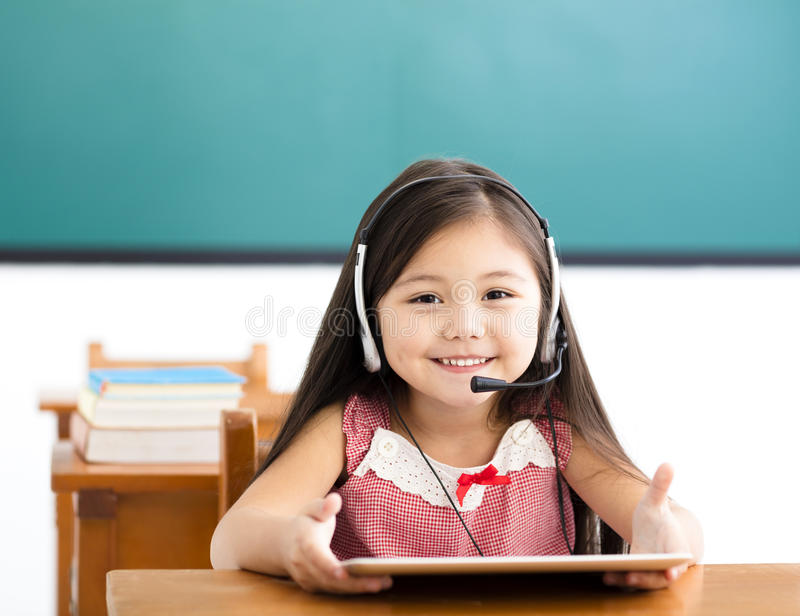niña que usa la tableta de Digitaces en clase imagen de archivo
