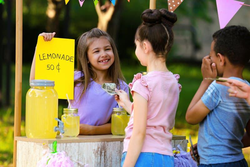 Niña que vende la limonada natural a los niños en parque Restauraci?n del verano imagenes de archivo