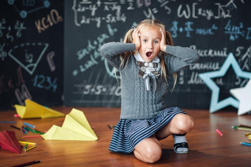 Niña rubia en el uniforme escolar que lleva a cabo las manos en su cabeza , abra su boca contra la pizarra con fórmulas de la esc imagen de archivo libre de regalías