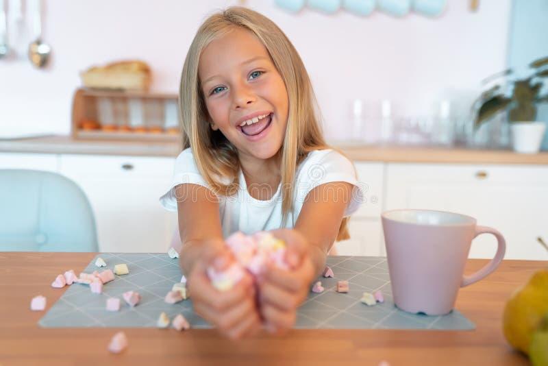 Niña rubia linda en la cocina tomando su desayuno divirtiéndose con malvavisco y sonriente. Esto es tan sabroso fotos de archivo