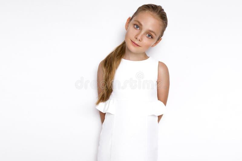 Niña rubia linda en un vestido elegante blanco, colocándose en un fondo blanco en estudio imagenes de archivo