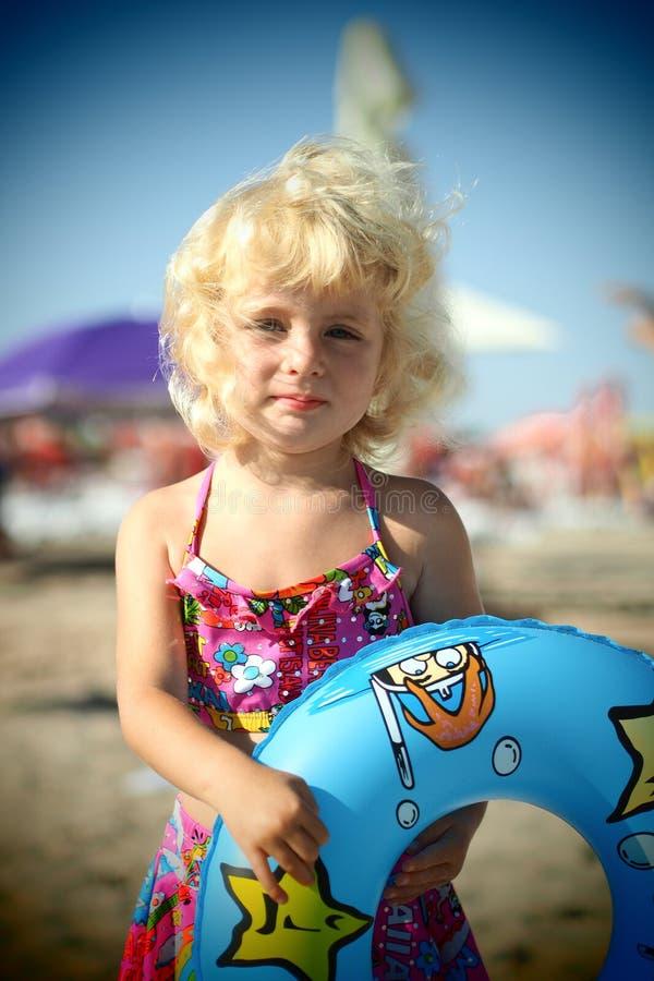 Niña rubia observada azul en la playa imagenes de archivo