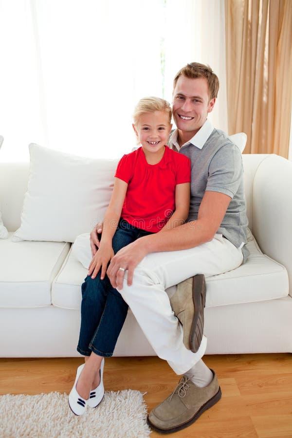 Niña rubia que se sienta en el sofá con su padre imagen de archivo