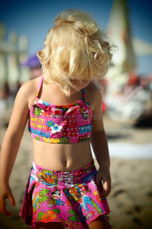 Niña rubia vestida agradable en la playa en el verano que mira abajo imagenes de archivo