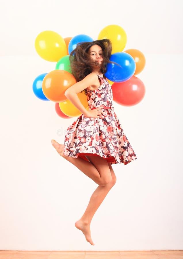 Niña saltando con globos inflados imagenes de archivo