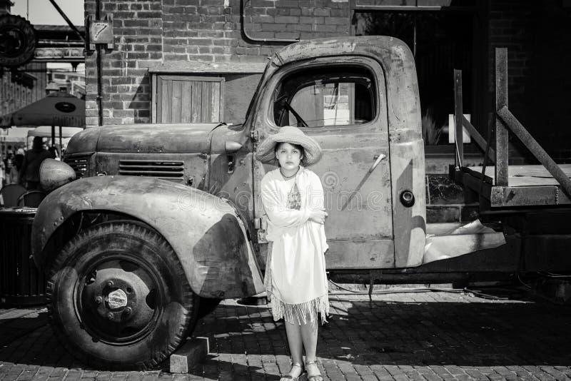 Niña seria hermosa que se coloca delante del camión retro del viejo vintage clásico fotos de archivo