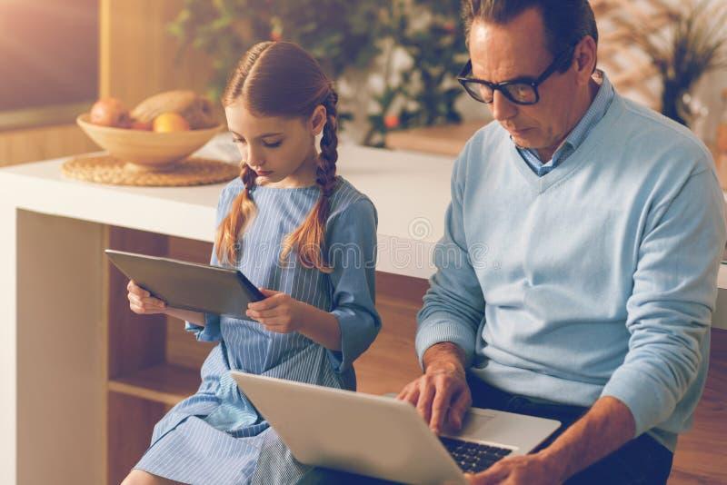 Niña seria y su papá que trabajan con los dispositivos digitales imagen de archivo libre de regalías