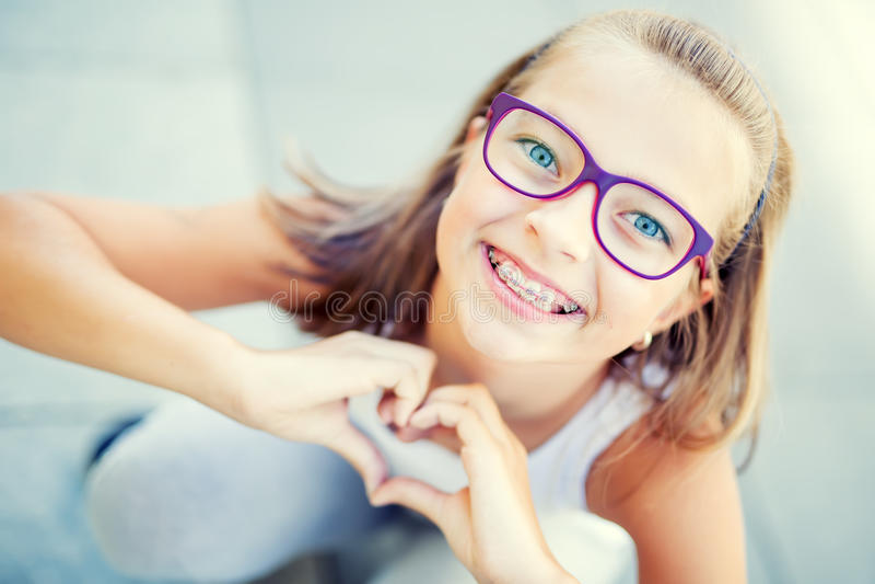 Niña sonriente adentro con los apoyos y los vidrios que muestran el corazón con las manos foto de archivo