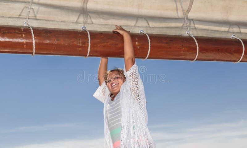 Niña sonriente alegre que coloca y que lleva a cabo el haz alto de la nave en fondo hermoso del cielo azul fotografía de archivo